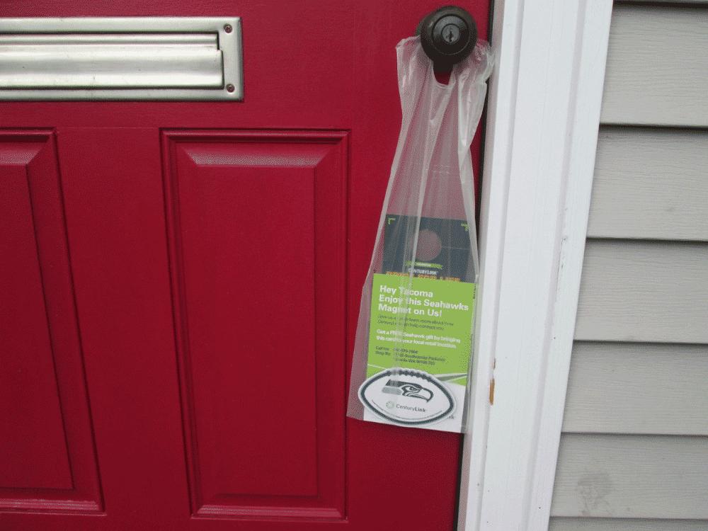 front door marketing media in a bag hanging on a front door